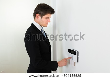 Young Handsome Businessman Entering Code In Security System - stock photo