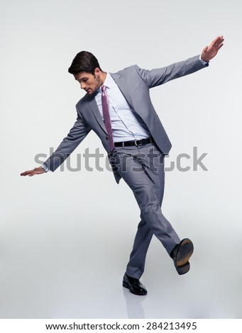 Young handsome businessman flying over gray background - stock photo