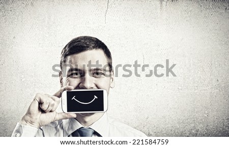 Young handsome businessman hiding mouth behind mobile phone - stock photo