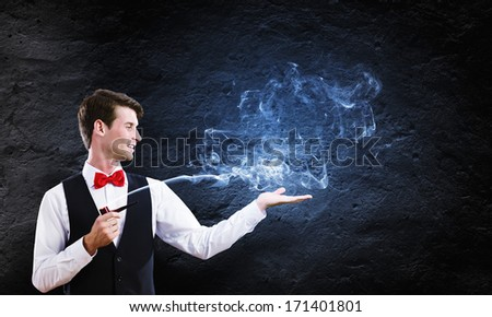 Young handsome businessman in fumes smoking pipe