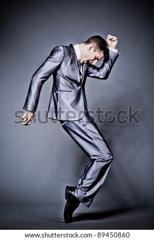 Young handsome businessman in silver suit dancing. - stock photo