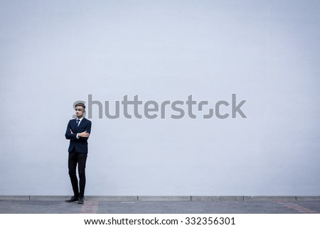 Young handsome businessman in suit standing outdoors