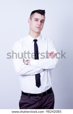 young handsome businessman in white shirt on gray background - stock photo
