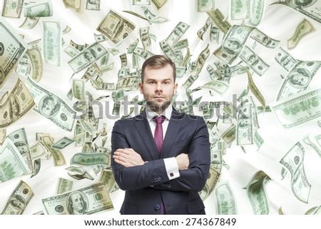 Young handsome businessman is standing over the falling down dollar notes. A concept of career success.