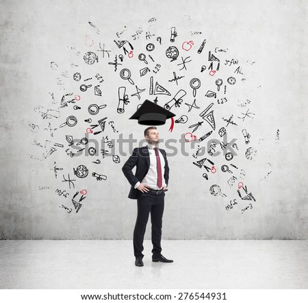 Young handsome businessman is thinking about education at business school. Drawn business icons over the concrete wall. Graduation hat. - stock photo