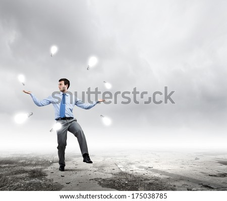 Young handsome businessman juggling with electrical bulb - stock photo