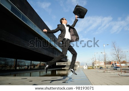 Young handsome businessman jumping in the street - stock photo