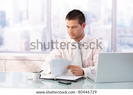 Young handsome businessman looking at organizer in bright office.?