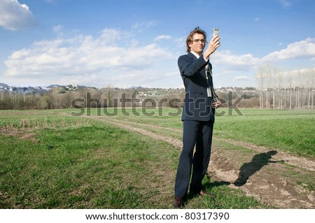 Young handsome businessman making photos with his mobile phone