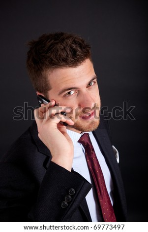Young handsome businessman on the phone against a dark background - stock photo