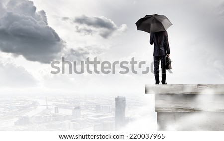 Young handsome businessman on top of building with umbrella - stock photo