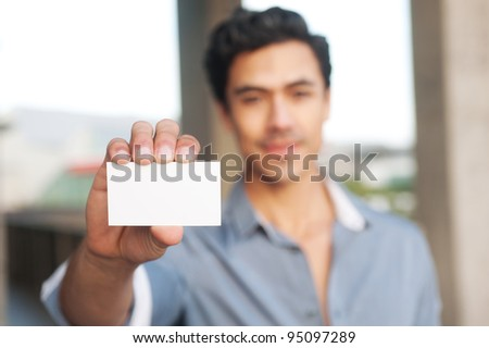 Young, handsome businessman presenting blank business card
