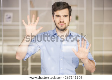 Young handsome businessman pressing on glass screen in office.