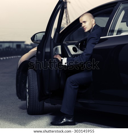 Young handsome businessman sitting in a car - stock photo