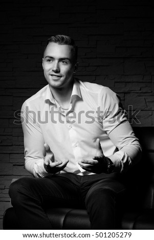 Young handsome businessman sitting on leather couch speaks and gestures