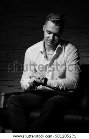 Young handsome businessman sitting with confidence on leather couch and looks to watches
