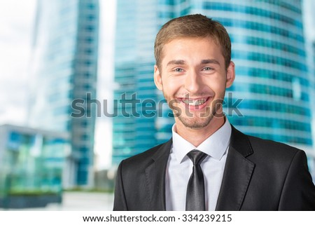 Young handsome businessman smiling - stock photo