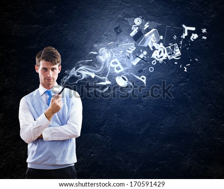 Young handsome businessman smoking pipe with business items at background - stock photo
