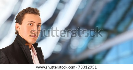 Young handsome businessman standing against a blue corporate blurred background - stock photo