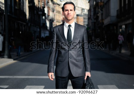 Young handsome businessman standing in the street - stock photo