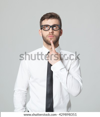 Young handsome businessman thinking while standing against gray background. - stock photo