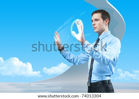 Young handsome businessman using futuristic hologram interface and keyboard in the bio style interior. - stock photo