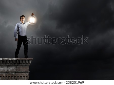 Young handsome businessman walking with lantern in darkness - stock photo