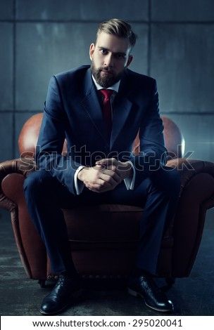 Young handsome businessman with beard in black suit sitting on chair and listens attentively to speaker. - stock photo