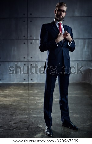 Young handsome businessman with beard in black suit standing on wall background. - stock photo