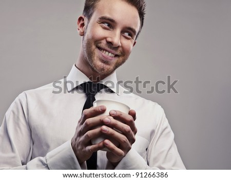 Young handsome businessman with cap of coffee. - stock photo