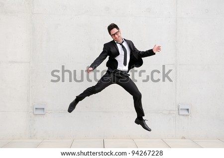 Young handsome businessman with eyeglasses jumping in the street - stock photo