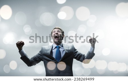Young handsome businessman with hands up celebrating success - stock photo