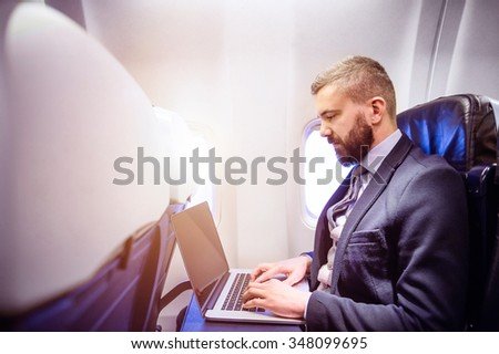 Young handsome businessman with notebook sitting inside an airplane - stock photo