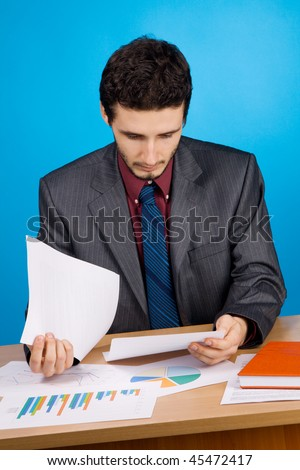 Young handsome businessman working with documents, blue background