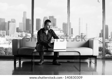 Young handsome casual business man working in a Penthouse Suite with Los Angeles Skyline behind him Black and White Image - stock photo