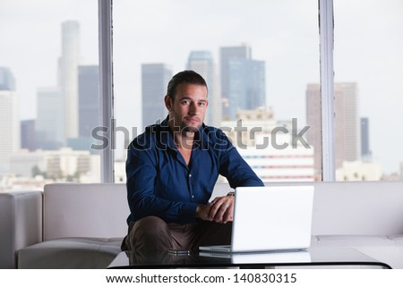 Young handsome casual business man working in a Penthouse Suite with Los Angeles Skyline behind him - stock photo