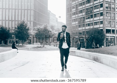 Young handsome caucasian black hair modern businessman walking in the city, smartphone handhold, looking down and tapping touchscreen - working, business, successful concept - black and white photo - stock photo