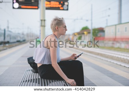 young handsome caucasian blonde italian designer sitting on a bench in railway station, using smart phone and smoking looking over - technology, social network, travel concept - stock photo