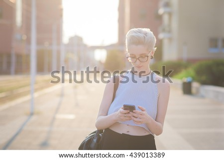 Young handsome caucasian blonde italian designer walking in the city backlight, looking down, holding a smartphone, pensive -  technology, social network, communication concept - stock photo