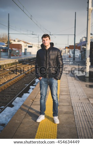 Young handsome caucasian brown hair man outdoor in the city posing with hand in pocket looking at camera on a platform - traveler, millennial concept - stock photo