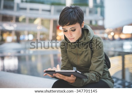 young handsome caucasian brown straight hair woman sitting in city dusk, holding tablet, looking downward screen, face illuminated by screen light - technology, social network, communication concept - stock photo