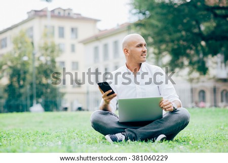Young handsome caucasian business man sitting in a city park using a laptop leaning on his knees and a smartphone handhold, overlooking - business, working, multitasking concept