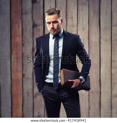 Young handsome caucasian man  dressed in suit and tie with ancient book. Studio portrait on wood background. Toned - stock photo