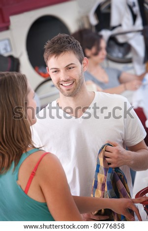 Young handsome Caucasian man flirts with woman in laundromat - stock photo