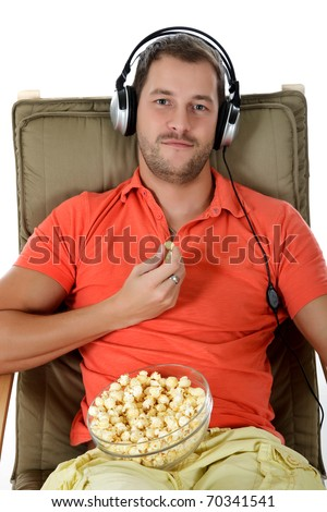 Young handsome caucasian man on sofa listening music at headphones and eating popcorn. Studio shot. White background. - stock photo