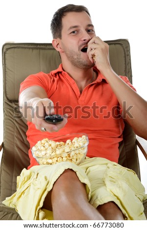 Young handsome caucasian man sitting on sofa holding a remote control and eating popcorn. Studio shot. White background. - stock photo