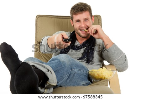 Young handsome caucasian man sitting on sofa holding a remote control and eating potatoes chips. Relaxation time. Studio shot. White background. - stock photo