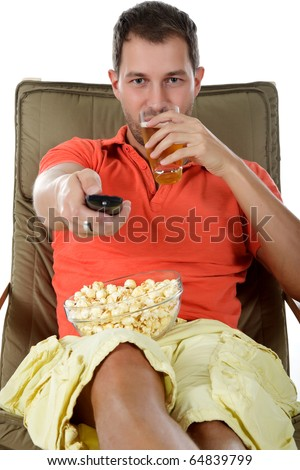Young handsome caucasian man sitting on sofa with popcorn, drinking beer and holding a remote control. Studio shot. White background. - stock photo