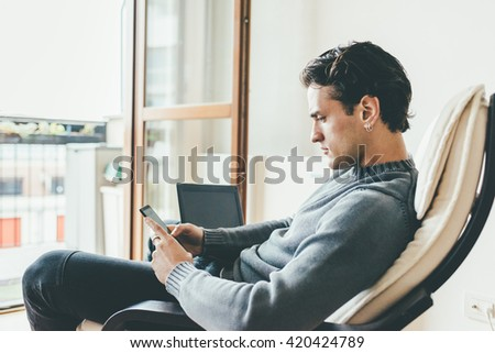 Young handsome caucasian man sitting on the sofa in his house using smart phone hand hold and notebook, looking down tapping the screen - business, technology, multitasking concept - stock photo