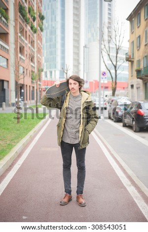 Young handsome caucasian man with moustache posing with his skateboard in the street of the city looking in camera - freshness, youth, carefreeness concept